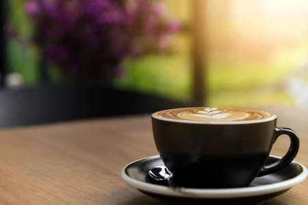 Nice cup of fresh brewed coffee with beautiful latte art on wooden table in cafe with copy space. Coffee break recreation relaxation