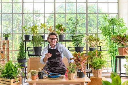 Happy senior man gardening wearing glasses and denim apron with digital tablet sitting in home gardening for looking who buys the tree. Small business concept.