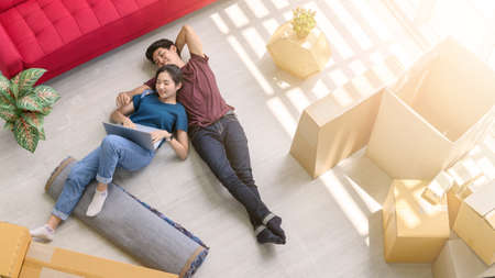 Top view of young asian couple working online marketing on laptop computer with cardboard parcel boxs of product for deliver at home. Start up online business concept