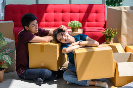 Young asian couple smiling, relaxing and resting on the floor after unpacking cardboard boxes in new house with cardboard boxes on floor Stock Photo