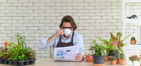 gardening wearing glasses and denim apron sitting and drinking coffee while reading newspaper in his home gardening. retirement lifestyle Stock Photo