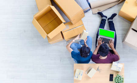 Top view of young asian couple working online shopping on laptop computer with cardboard parcel boxs of product for deliver at home. Start up online business concept. green screen computer