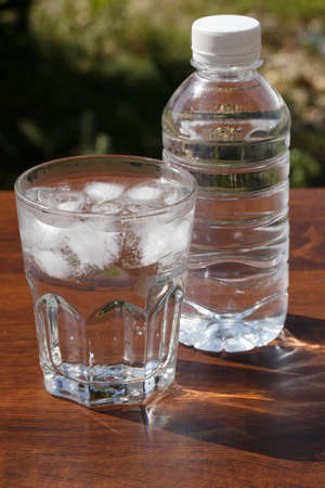 purified: a glass of water and ice cube on wood table Stock Photo