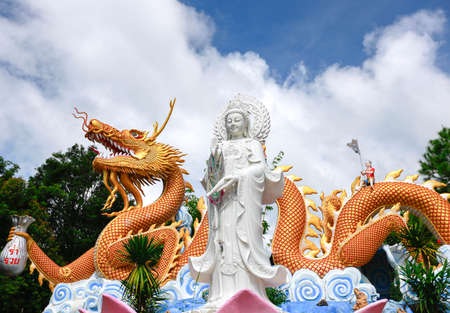 guanyin scalpture standing in front off golden dragon   photo