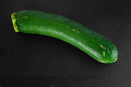Zuchini on slate plate isolated in the kitchen against a black background