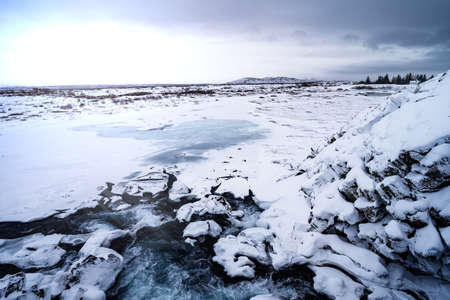 Snow and ice landscape in Iceland in winter with a distant view water flow