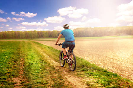 Cyclists cycling, cycling. In the park with grass in the background and forest. sunlight whit shine. beutiful spring mountain