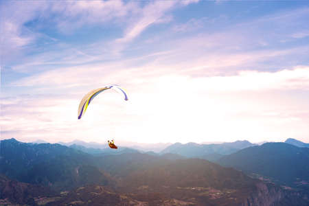 Paraglider flies over Italian mountain