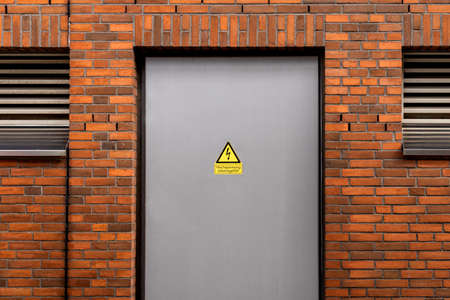 attention danger to life warning sign on a door in front of a technical room. yellow warning sign near building with bricks.
