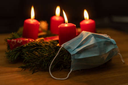 christmas advent wreath with a protective mask, concept christmas 2020 with corona virus.