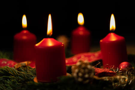 red advent candle burns on christmas wreath.