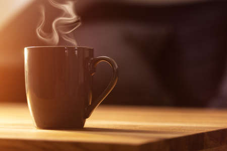 gray cup of coffee on brown wooden table. morning sunshine. coffee for breakfast. hot coffee.