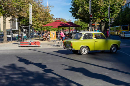 BERLIN, GERMANY - September 18, 2020, people wait at a traffic light in Berlin while a green trabbie turns around.