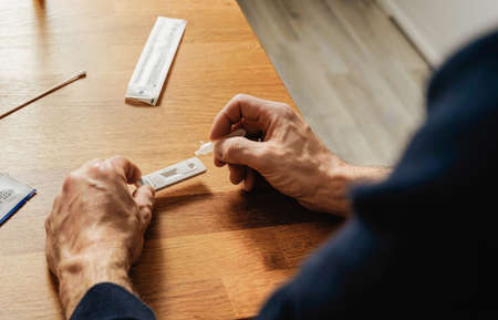 quick home test - man uses a test cassette and tests himself for virus infection.