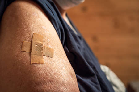 overweight woman shows her arm after being vaccinated. arm with adhesive bandage after injection. Health concept