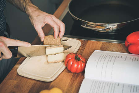 young man cuts tofu in the kitchen on a cutting board with a knife - cooking a vegan recipe from a cookbook. cut tofu into slices.