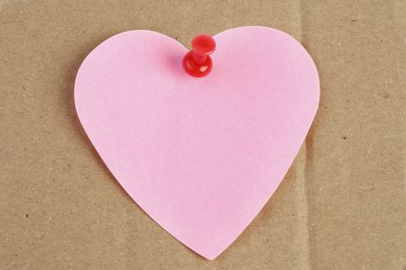 heart shaped post-it on brown cardboard Stock Photo