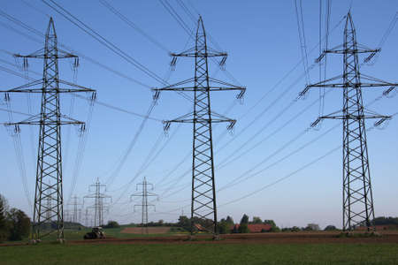 power lines on farmland with a trector and blue skies Stock Photo