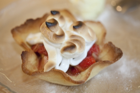 Dessert made of shortcrust pastry  with strawberry - rhubarb filling and topping of meringue made of egg white fresh out of the oven