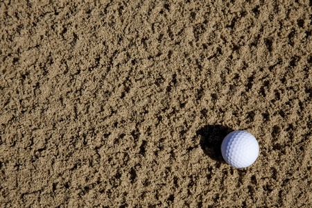 a golfball lying in a sand bunker on a golf course