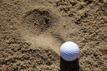 a golfball landing in a sand bunker on a golf course Stock Photo