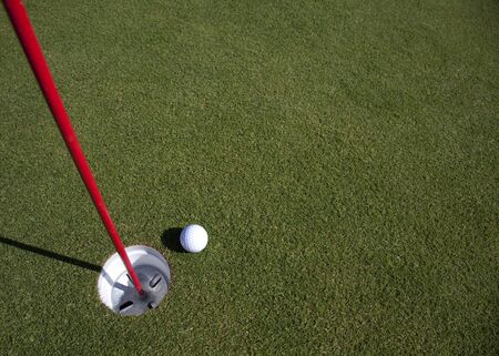 A golfball comes to rest near the hole - with copyspace in the green