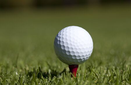 A white Golf ball sits on a red wooden tee on green grass