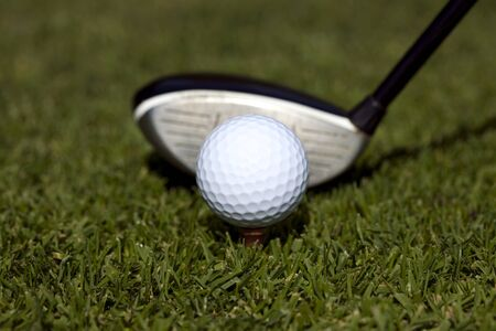 Close up of a golfball on a tee with a three wood