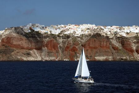 mediterranian: Sailboat on Mediterranian sea with Santorini village of Oia in background