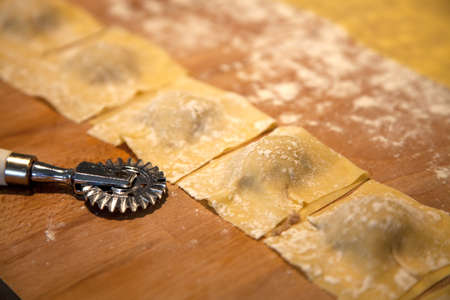 Preparation of homemade Ravioli with veal filling on wooden plate - shallow depth of field Stock Photo