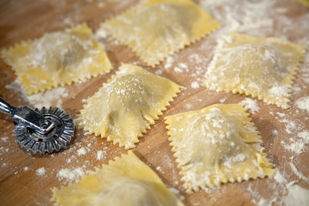 Preparation of homemade Ravioli with veal stuffing on wooden plate - shallow depth of field