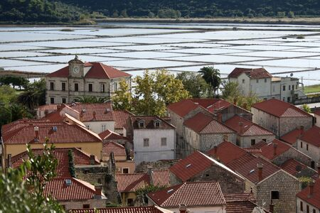 Medieval Croatian town of Ston with salt production lakes in background