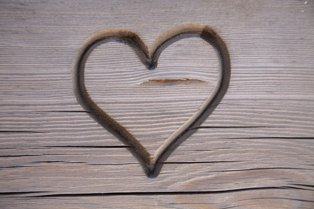 Perfect heart carved in a wooden park bench Stock Photo