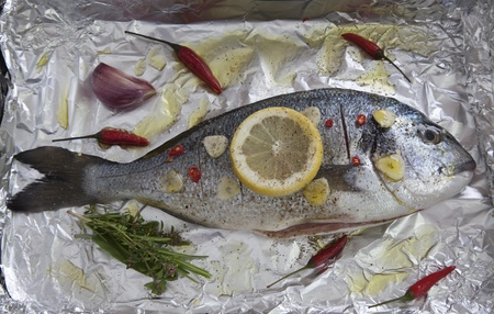 Gilthead sea bream  sparus aurata  with lemon, herbs, garlic and chili on aluminum foil ready to be cooked