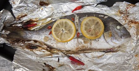 cooked gilthead sea bream with lemon, garlic, and chili Stock Photo
