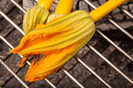 Fresh organic zucchini flowers on an outdoor grill