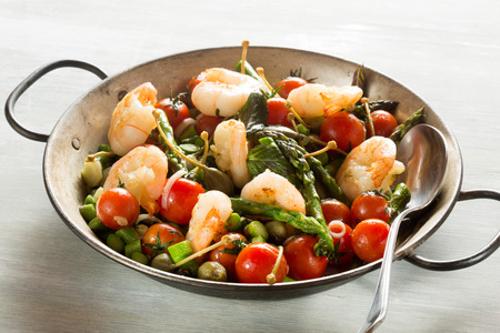 Stir-fry of Shrimps, green asparagus, capers, spring onion and peppermint in old pan