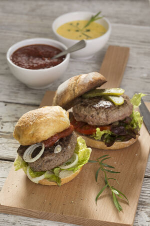 fresh grilled hamburgers with ketchup and sauce hollandaise, pickles and salad