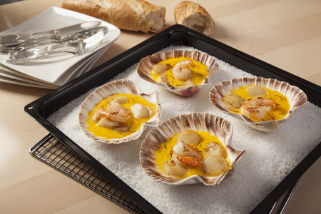 shrimps and scallops in saffron sauce baked in empty shells  on a bed of sea salt Stock Photo