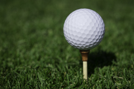 Golfball on wooden tee Stock Photo