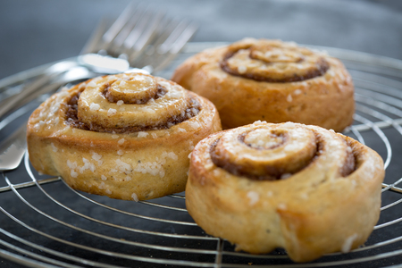 Cinnamon buns on rustic baking plate Stock Photo