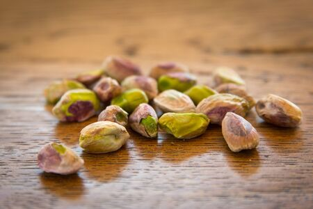 pistachio nuts without their shells on a wooden table Stock Photo