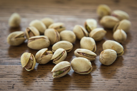 pistachio nuts in their shells on a wooden table Stock Photo
