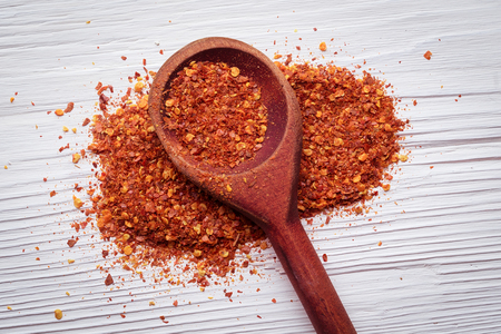 Ground hot thai chilli powder and flakes on a white wooden background.