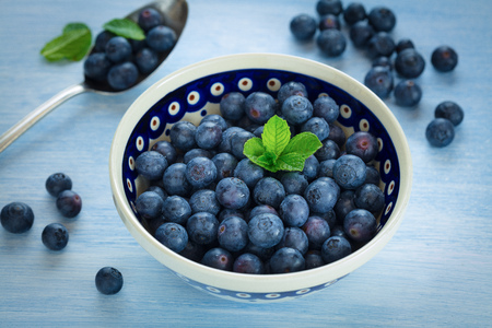 Fresh blueberries in a bowl on blue background Stock Photo