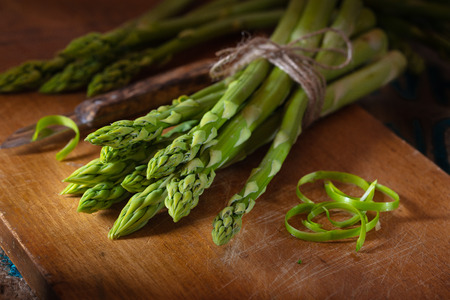 green asparagus on a wooden plate Stock Photo