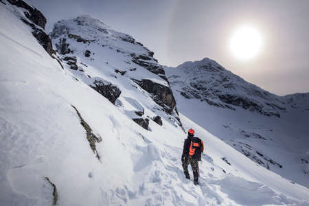 Climber hiking on the mountain in winter. Tatra Mountains with KoÅ›cielec peak. Snowy scenery. Banque d'images - 148168343