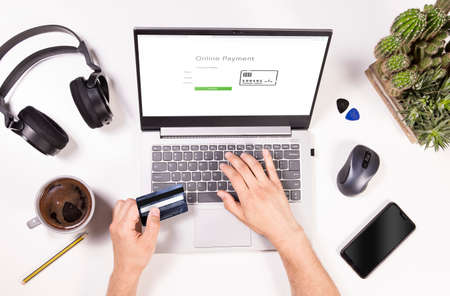 Online payments top view concept. Man is shopping online and paying with credit card. Desk flat lay view with laptop, mobile, coffee, headphones and mans hands.