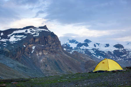 Base camp set in Alpine background in Breuil Cervinia. Ten set on hill i Alps mountains. Tourist shelter camp in high mountains.