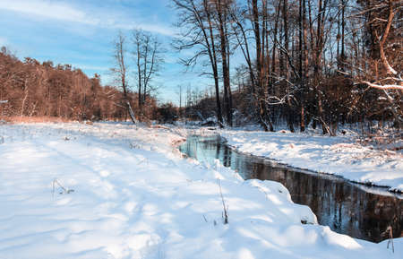 Winter landscape in Poland. Snowy outdoors nature with river and forest. Cold sunny day.